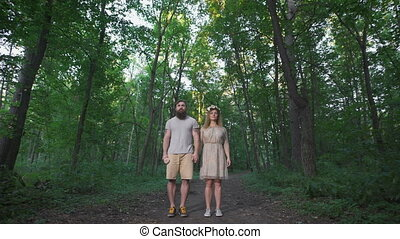 Man standing in the woods with his girlfriend. They are...