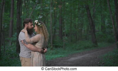 Tattooed guy with his cute girl in the forest. They hug each...