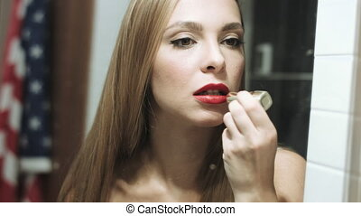 Beautiful blond woman paints her lips