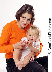 Mather in orange T-shirt with little blonde girl on the white background