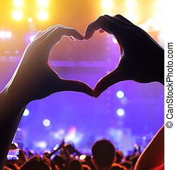 Silhouette of a heart shaped hands and crowd of Audience at...