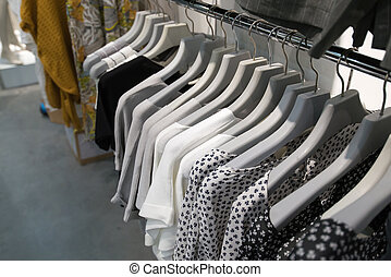 Clothes hang on a shelf in store