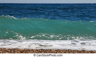 Background of waves of the sea on the beautiful pebble beach.