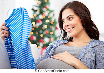 happy woman holding baby boys bodysuit at home - holidays,...