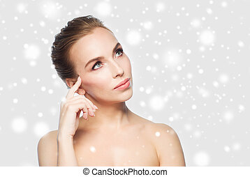 beautiful young woman touching her face over snow - beauty,...