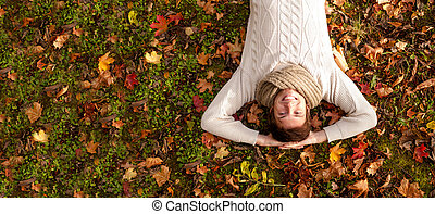 smiling young man lying on ground in autumn park - season,...