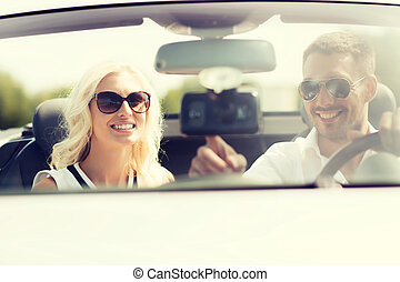 happy couple usin gps navigation system in car