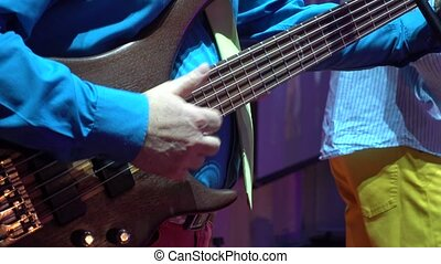 Man plays bass guitar on the stage