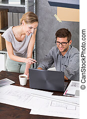 Woman is standing next to her co-worker who is working on his laptop