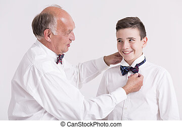 Elegant grandfather helping his grandon with collar - Young...