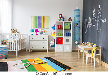 Spacious colorful child room with cradle and blackboard wall