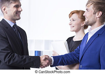 Elegant man shaking employee's hand - Elegant and smiled man...