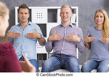 Young people learning sign language - Shot of smiling young...