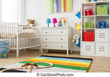 Baby room with white cradle and chest of drawers - View of...