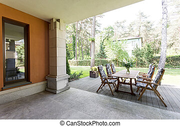Veranda with wooden table and chairs - Veranda of a...