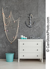 Sea inspired interior with white commode, fishing net and...