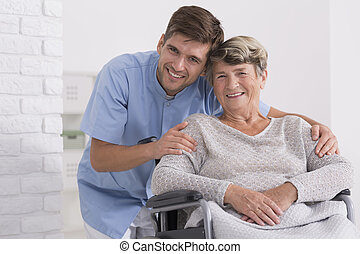 Male nurse hugging his senior woman patient sitting on a...