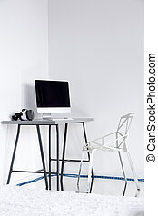 Minimalistic white room with chair and desktop
