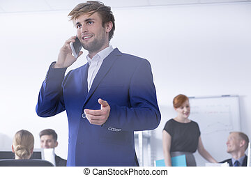 Man in suit talking on phone at office - Closer shot of a...