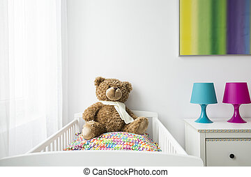 Child room with a cradle and teddy bear - View of part of a...