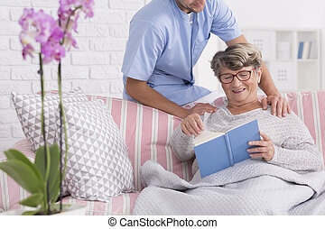 Caregiver with senior reading a book
