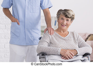 Caregiver and woman on wheelchair with a hand on her shoulder