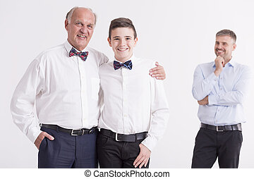 Boy standing close to his grandfather - Young boy standing...