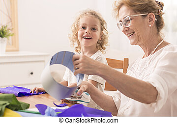 Grandmother making paper cuts - Grandmother making the paper...