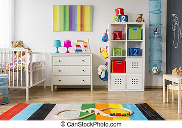 Colorful and pretty child room with chest of drawers and...
