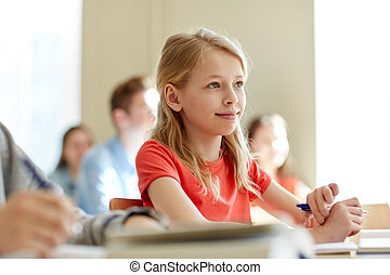 group of students with notebooks at school lesson -...