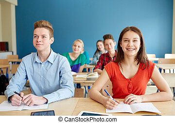 happy students with notebooks at school - education,...
