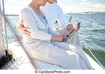 senior couple with tablet pc on sail boat or yacht -...