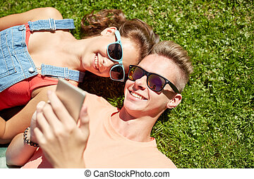 happy teenage couple smartphone lying on grass - love and...