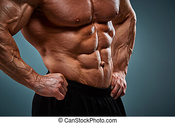 torso of attractive male body builder on gray background. -...