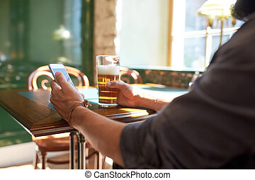 close up of man with smartphone and beer at pub - people,...
