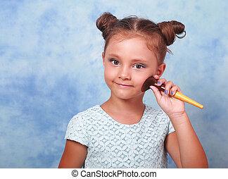 Cute beautiful small kid girl applying tonal cosmetic on the...