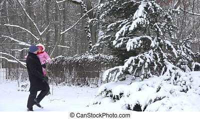 Man with baby child shake off snow from fir tree branches in...