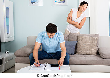 Woman Peeking From Behind While Man Calculating Bills -...