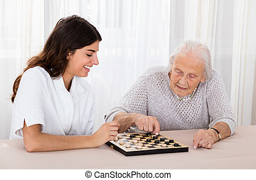 Two Women Playing Checkers Game - Senior Woman Playing...