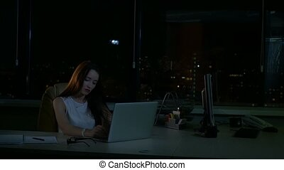 A woman works in the office at the computer at a later time