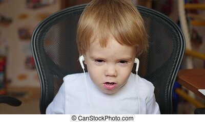 the little child listens to music on smartphone in the headphones in home