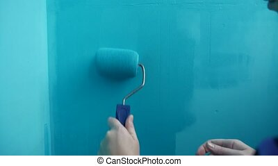 woman paints the wall roller blue, work artist painter for...