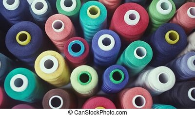 Row of colorful thread spools on table. Bright colors -...
