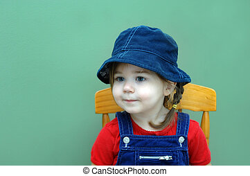 Absorbed in Imagination - Little girl, wearing a denim cap...