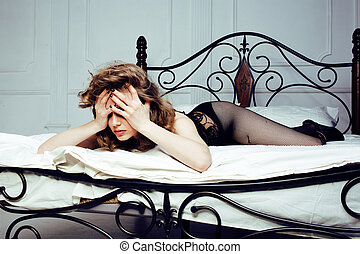 crying woman laying in bed, winter depression holding head...