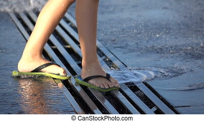 Children's feet in flip flops in a spray of water from a fountain