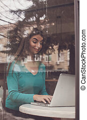Freelancer is typing - Through glass woman-freelancer is...
