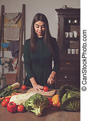 Woman and vegetables - By a woman a tomato is cuted