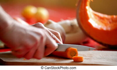 slicing carrot - close up on man\'s hand slicing carrot on...