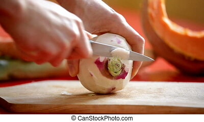 cutting turnip - close up on mans hand slicing turnip on...